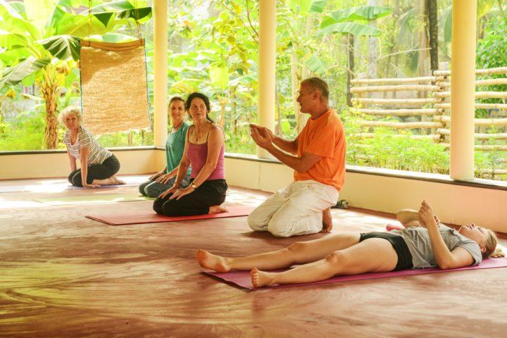 Teaching yoga students during asana class